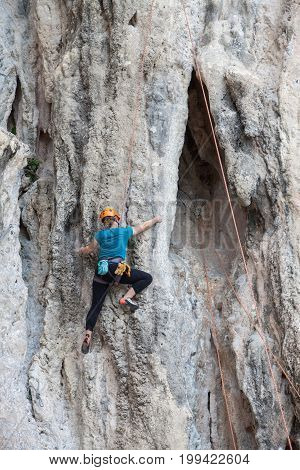 Tourist Woman Climbing On A Limestone Wall On Krabi Province At Thailand.