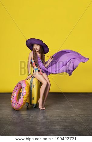 girl in a swimsuit in a hat with a suitcase.
