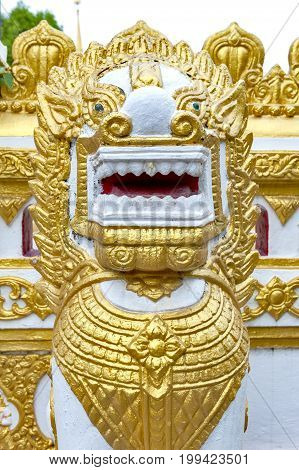 Statue of golden Singha or lion guardian situated in temple of Phra That Phanom Nakhon Phanom Province northeastern Thailand