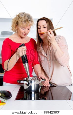 Young Woman And Her Mother Together In The Kitchen