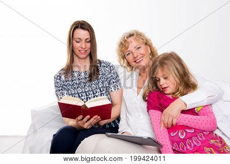 Woman With Daughter And Grandchild Together Reading In Book And Tablet Pc