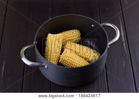 yellow gold colorful sweet maize corn boiling cooking in a large aluminum pot with charcoal outdoor on a pathway i