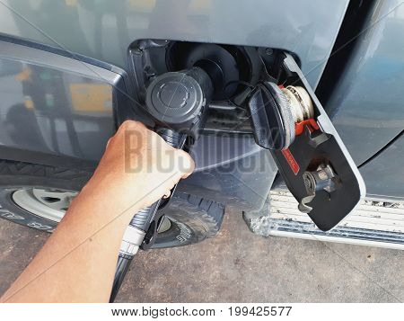 JOHOR, MALAYSIA - AUGUST 9th, 2017: A hand holding fuel pump nozzle at fuel station.