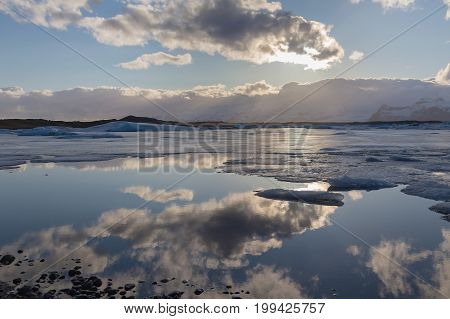 Reflection water season lagoon with sunset behind cloud Iceland natural landscape background