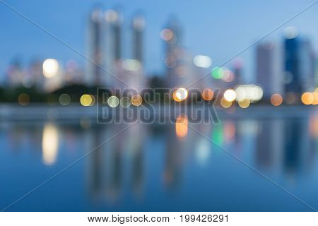 Blue twilight blurred bokeh light office building water front abstract background