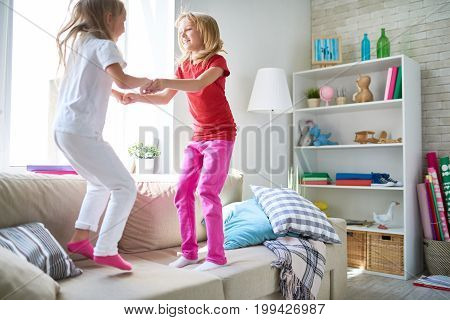 Two fidgety children holding hands and jumping on cozy couch while enjoying each others company in spacious living room