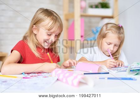 Pretty little participants of drawing class sitting at desk and coloring pictures with felt-tip pens, blurred background