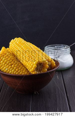 Homemade golden corn cob with salt on black background