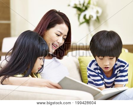 asian mother sitting on couch at home reading book with son and daughter.