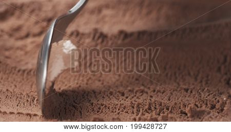 closeup scooping chocolate ice cream with spoon, wide photo