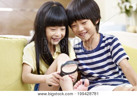 two asian children sitting on couch at home having fun playing with a magnifying glass.