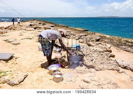 Tour to the sandy Bazaruto island in Bazaruto Archipelago with local people grilling barracuda fish next to the ocean. Mozambique, Africa.February 2017