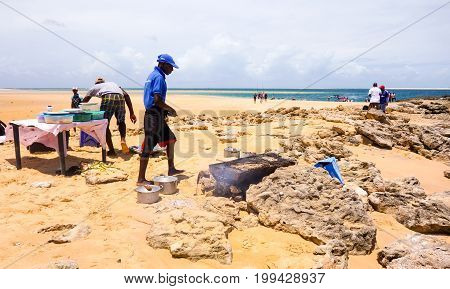 Tour to the sandy Bazaruto island in Bazaruto Archipelago with local people grilling barracuda fish.Mozambique, Africa.February 2017