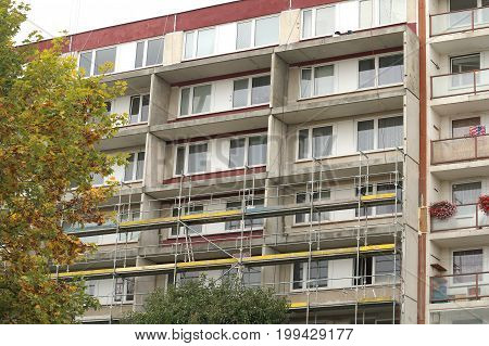 Old socialistic house of flat (prefabricated panel house) under reconstruion of its exterior and adding balcony to each apartment scaffolding under construction