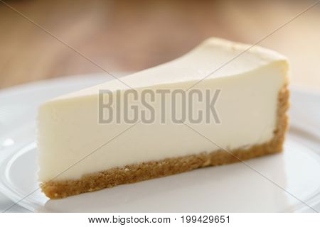 slice of traditional new york cheesecake on white plate on wood table, shallow focus