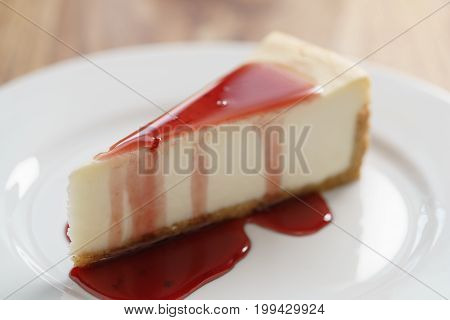 raditional new york cheesecake with berry jam on white plate on wood table, shallow focus