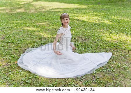 Beautiful bride in white lace dress sitting on green grass