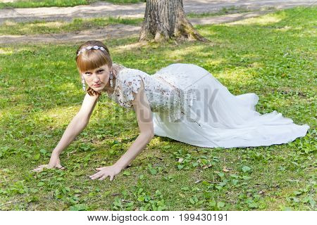 Bride in white lace dress crawl on green grass at the summer time
