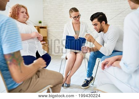 Portrait of young man crying in support circle of group therapy meeting sharing problems with female psychiatrist