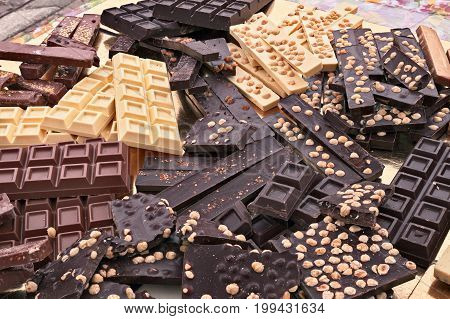 pile of assorted chocolate bars - heap of black and white chocolate pieces with hazelnuts