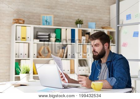 Portrait of modern bearded businessman in casual wear using video call while working with laptop in modern office, discussing documentation via internet