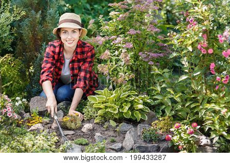 young woman gardener care of flowers in the garden. Girl weeding weeds in flowerbed. People, gardening, care of flowers, hobby concept