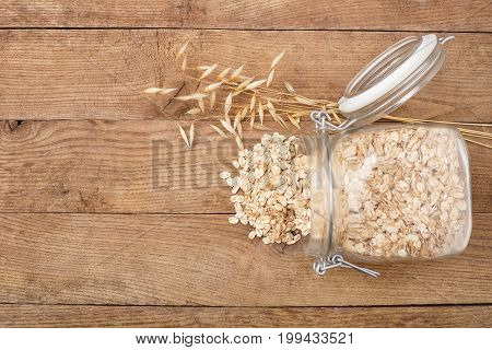 oat flakes in glass jar and oat ear on wooden table top view. Uncooked oatmeal