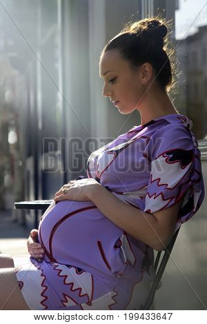 Beautiful pregnant young woman in street- cafe