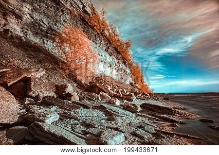 Rocky sea shore with surrealistic colors. IR photography.