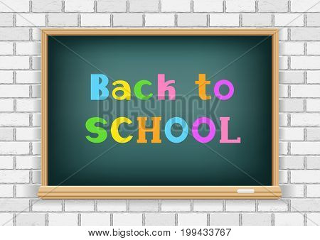 Back to school multicolor text message on school blackboard on white brick wall background. Education chalkboard and white chalk