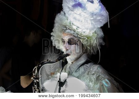 Undefined Man In Glowed Dress Play On Saxophone
