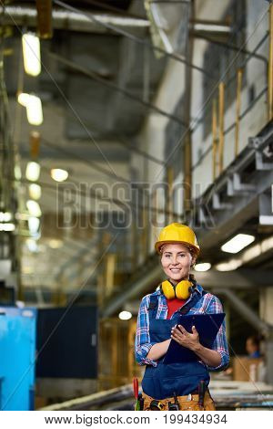 Portrait of young woman in hardhat working in modern plant, smiling at camera holding clipboard