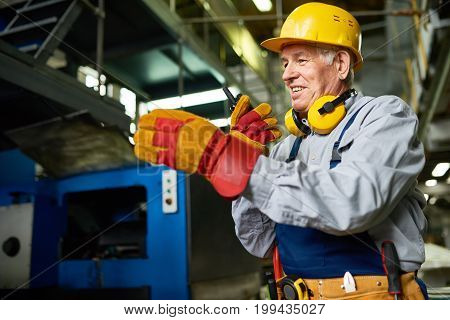 Portrait of senior factory worker using portable radio set and smiling talking to somebody in workshop