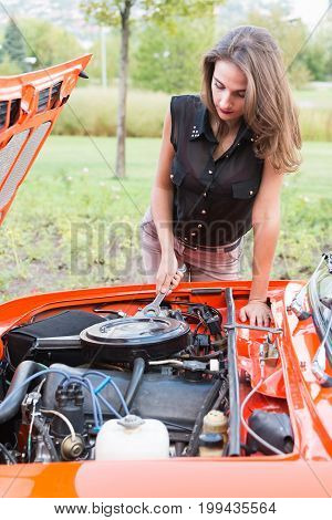 Girl with a wrench looks at an old car engine