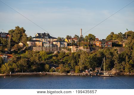 View on luxury cottages and private boat along Stockholm archipelago, Sweden. Summer sunset time.
