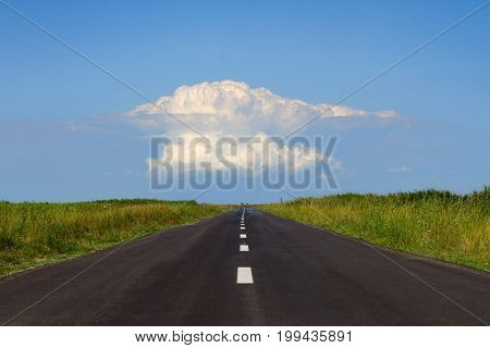horizontal perspective view of black asphalt road with a large white cloud at the horizon against a blue sky