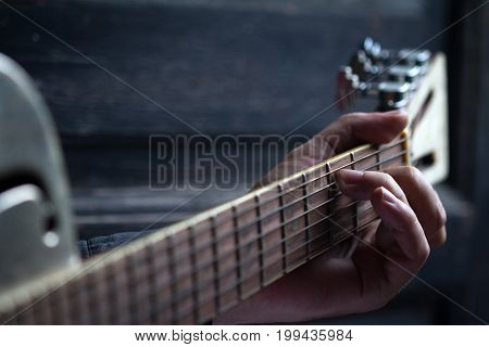 fingers playing acoustic guitar on black dark wooden background with selective focus