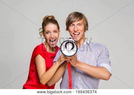 beautiful happy young couple  screaming at megaphone. handsome man and girl together. copy space.