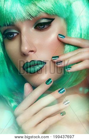 beautiful young woman with fancy makeup in green wig. Beauty shot, closeup. hands with green nails.