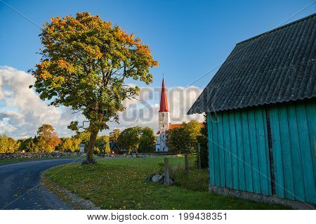 Bellfry and ancient Lutheran church in Kihelkonna, Saaremaa, Estonia. Early autumn sunny day. Village view with road, tree and barn poster