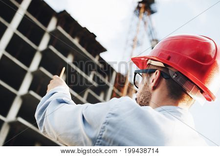 Young Businessman Directs The Construction Of Skyscraper. Architect Inspects Construction Site