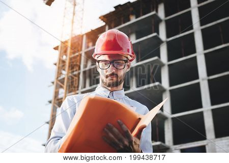 Engineer Or Architect With A Folder Of Documents In Hand. Inspector Inspects The Skyscraper Under Co