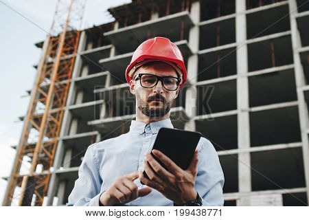 Young Business Man Builder In Red Hard Hat With Tablet In Hand. Portrait Engineer Or Architect With