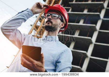 Bearded Young Modern Engineer Builder With Tablet Gadget In Hand Inspects Construction Of Skyscraper