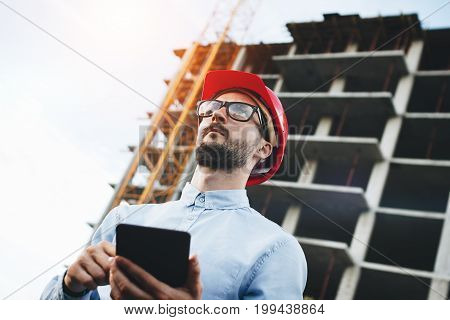 Young Engineer In Red Hard Hat With Tablet In Hands At Construction Site. Inspector With Electronic