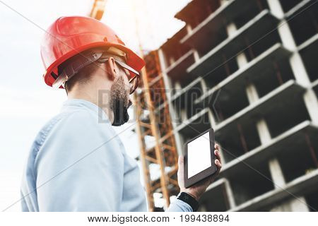 Engineer In Helmet On Construction Of New Modern Enterprise With Tablet In Hand. Concept Of Modern A