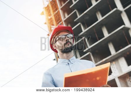 Portrait Of Modern Male Engineer At Construction Site Of New Modern Plant. Inspector Holds A Folder