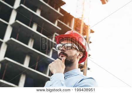 Thoughtful Engineer In Red Hard Hat Thinks Over Construction Building. Portrait Of Architect In Glas