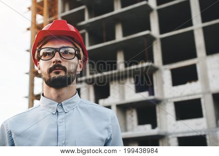Portrait Of Engineer Or Architect Wearing Glasses And Hard Hat At Construction Site Of New Modern Fa