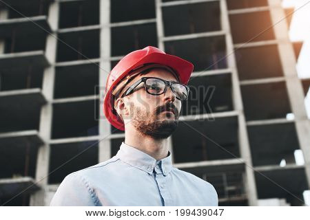 Young Successful Businessman Builder With Glasses And Red Hard Hat On Construction Site Inspects Con